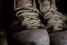 Closeup Of Vintage Used Hiking Boots Hanging From Tree In Forest