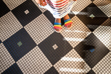 Feet Of Child In Rainbow Sandals On Tile Floor