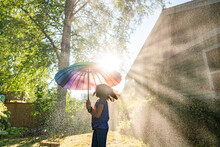 Twirling Girl With Rainbow Umbrella