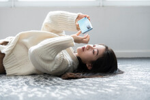 A Woman Is Lying On The Carpet Playing With Her Cell Phone