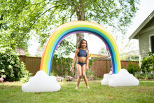 Curly Haired Girl Poses Under Rainbow Sprinkler