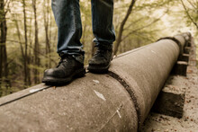 Closeup Of Boots Walking On Top Of Pipeline In Forest