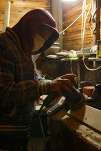 Man In Mask Polishing Wood On Workbench