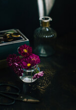 Still Life With Cut Flowers, Glass Bottle And Book