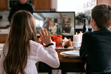 Thanksgiving: Girl Waves To Distanced Relatives On Monitor