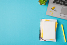 Top View Photo Of Workplace With Laptop Yellow Chancellery Notebooks Plant On Isolated Blue Background With Copyspace