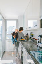 Mother With Kid Washing Dishes In Kitchen
