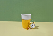 Small Alarm Clock Near Reusable Ceramic Cup For Drinks.