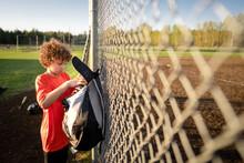 Boy Loads Baseball Glove Into Bag