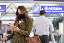 Travel: Woman Using Cell Phone To Check Flight Information