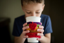 Boy Holds Cup With Crocheted Cozy