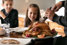 Thanksgiving: Father Carves Turkey While Hungry Kids Watch