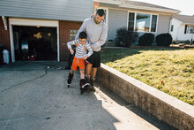Dad Helping Young Son Rollerblade Up The Driveway.