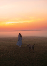 A Girl With A Long Hair Walking In The Middle Of The Foggy And Misty Field With A Dog Following A Girl N The Early Morning With An Orange Red Sky