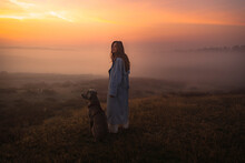 A Girl With A Long Hair Wearing A Long Blue Coat Standing In The Middle Of The Foggy And Misty Field With A Dog In The Early Morning With An Orange Red Sky