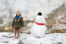 Little Girl Smiling Posing Next To A Snowman Over Old Broken Concrete Wall