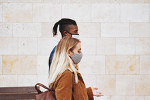 Young Couple In Masks Walking Outside