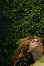 Curly Young Woman Resting On Green Grass