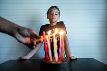 Boy Watches Man Light Birthday Candles