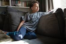 Boy Looks Out Window In Living Room