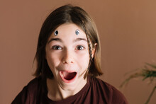 Surprised Girl With Eye Stickers On Her Forehead