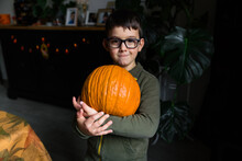 Little Boy Holding A Big Pumpkin On His Arms