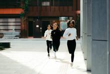 Smiling Friends Running Along A Sidewalk