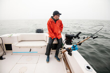 Man In Raincoat On A Boat With A Fishing Rod In The Fog