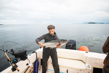 Woman Holding A Fresh Salmon On A Boat In The Ocean