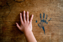 Child Holds Large Hand Next To Smaller Handprint