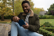 Young Mixrace Man Reading An E-Book In The Park