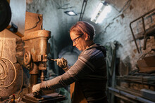 Woman Blacksmith Works In Her Workshop