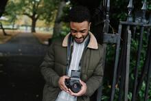 Man Standing Beside A Park Gate Holding A Film Camera