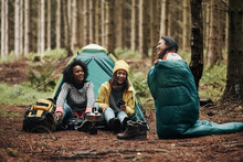 Friends Laughing While Camping In The Woods
