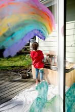 Girl Painting Rainbow Mural On Sliding Door