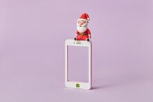 Plasticine Santa Claus Sits On A Smatrphone Frame.