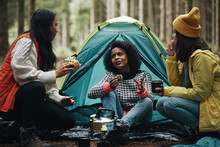 Friends Eating Dinner At Their Campsite