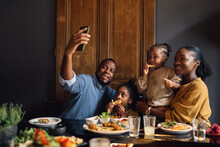 A Dad Taking A Selfie Photo Of His Family In A Restaurant