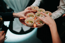 Waiter Serving Appetizer Dishes In Small Ceramic Cups To Female Guests
