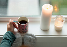Female Hand Holding A Handpainted Cup Of Tea On Window Sill