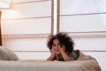 Girl Laughing On A Cozy Bed