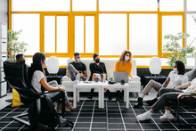 Group Of Diverse Coworkers Wearing Face Masks Chilling And Talking During Coffee Break In A Modern And Bright Workspace