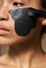 Woman Applying Black Cosmetic Mask On Face