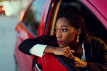 Young Woman Inside A Car At Night Popping Out Her Head Through The Window.
