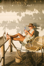 Woman Relaxing At Cafe By The Sea