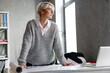 Leinwandbild Motiv White-haired focused woman examining drawing while standing in office
