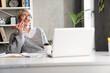 Leinwandbild Motiv Smiling woman talking on mobile phone while working with laptop