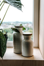 Two Pottery Jars With Lid On A Window Sill With House Plant
