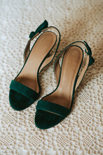 Green High Heel Shoes On A Vintage Bedspread