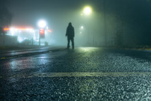 A Low Angle, Shallow Depth Of Field, Of A Hooded Figure Standing In The Road